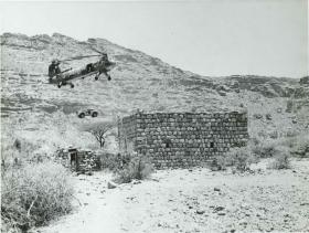 RAF Belvedere Helicopter winches a land rover into an accessible wadi in Radfan.
