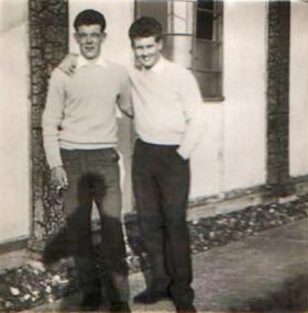 Two soldiers pose outside PCAU Living Quarters. 1955.