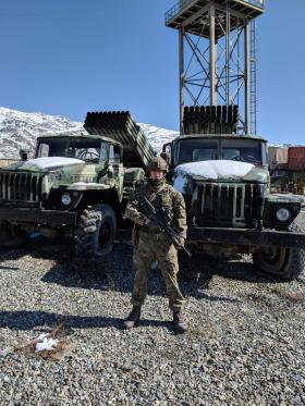 Pte Josh Lewis in front of 2 Russian Trucks