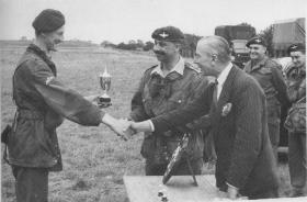 Col 'Boy' Wilson presents Pte Grundy with the Wilson Trophy - Cpt Joe Smith assists with Capt Bennett and Lt Lumby looking on