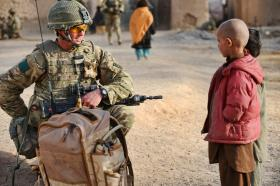 A soldier from 3 PARA talks with a local child, Naqilabad Kalay, Afghanistan, 2011