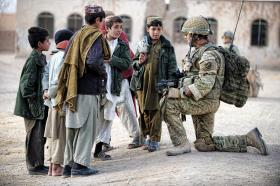 A soldier from 3 PARA talks with local children, Naqilabad Kalay, Afghanistan, 2011
