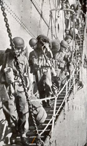1st Parachute Brigade disembark from a ship in Algiers in November 1942. They are carrying bags on their shoulders.