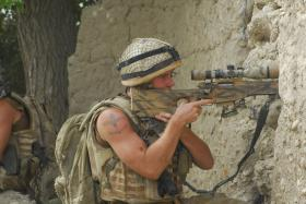 2 PARA sniper in action firing through a compound wall, Afghanistan, 2008
