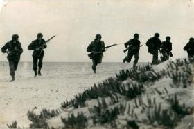 Seven men from 1st Airborne Division run along sandy terrain, North Africa, 1943