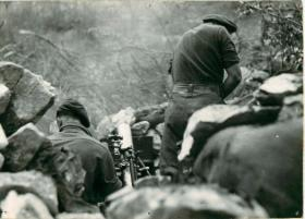 Two mortar crew get their 3 inch mortar in position.