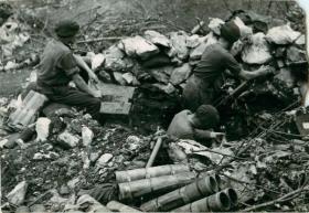 Three mortar crew get their 3 inch mortar in position.