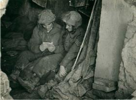 Privates Madden and Williams rest on the floor with a book.