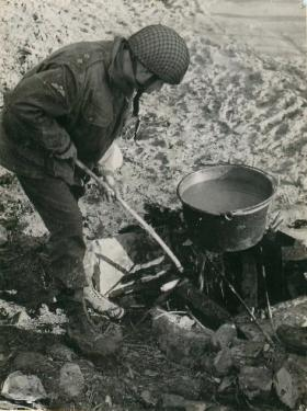 Lieutenant Stanning makes soup on a fire among rocks.