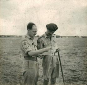 Brigadier Prichard reads a document with the brigade chief clerk.