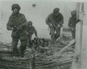 Four paratroopers amid debris in Oosterbeek.