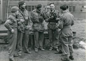 Three war correspondents in uniform and with cameras talk to their colleagues.
