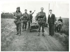 Paratroopers pose with Dutch civilians on a track between fields.