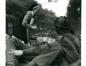 A Dutch nurse giving first aid to a wounded paratrooper.