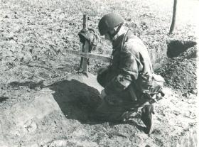 Corporal Mills pays his respect to the grave of Trooper Edmond, 1944.