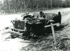 Burnt out Jeep on side of road. A wooden cross stands in the foreground.