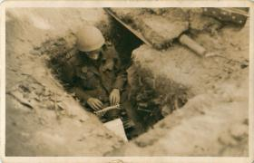 War correspondant Alan Wood sits in a trench with his typewriter in the grounds of the Hartenstein Hotel.