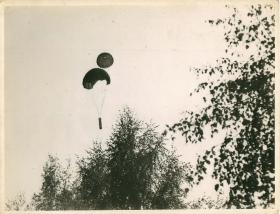Resupply container being parachuted to soldiers on the ground.
