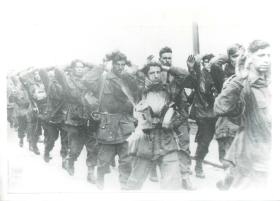 Captured British paratroopers march to captivity with their hands on their heads.