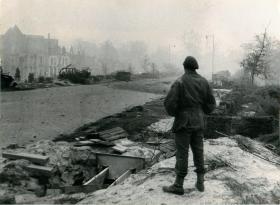 Paratrooper looks at the still destroyed Arnhem over 6 months after the battle.