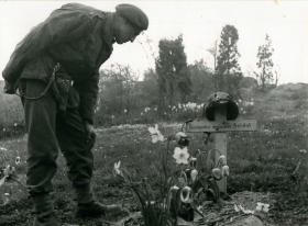 An airborne soldier looks at the grave of an unknown soldier in Arnhem, April 15th 1945.