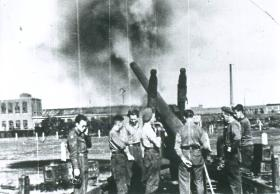 Seven men of 64 Medium Regiment RA fire from the power station at Nijmegen with a 5.5 inch gun.