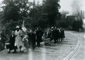Dutch civilians are evacuated from St. Elizabeth's Hospital by a medic waving a white flag.