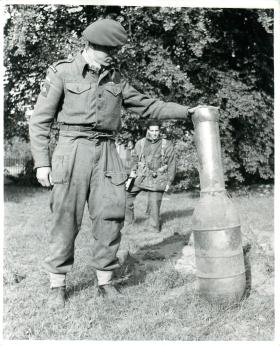 Airborne Signaller holds unexploded German rocket in Hartenstein Hotel grounds, September 1944.