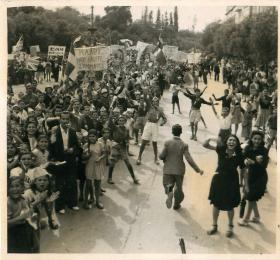 Greek civilians crowd in the streets to welcome British paratroopers.