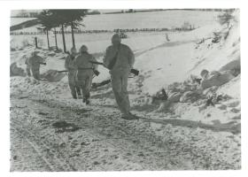 Covered by bren gunner and rifleman, recce patrol move towards new position. Jan 1945.
