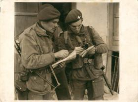 Maj Barnes and Lt Watson consult maps before an attack in Athens. 23 December 1944