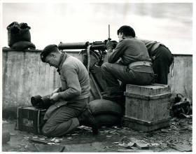 Paratroopers fire Vickers machine guns from roof of KKE building in Athens.