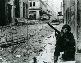 A soldier crouches with his gun in a street destroyed by fighting.
