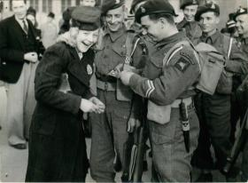 A Norwegian girl obtains autographs from men of the 1st Airborne Landing Brigade.