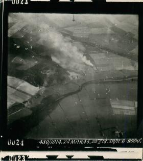 Aerial photo showing aircraft dropping parachutes carrying containers before men drop.
