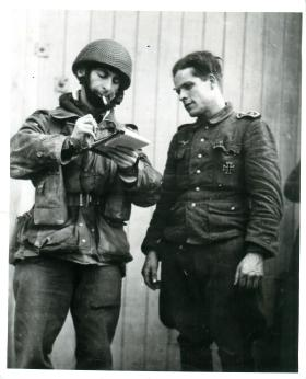 A British para takes the details of one of the first Germans taken prisoner in the Rhine operations.