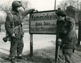 Two British airborne men by the sign for Hamminkeln the day they took the town.