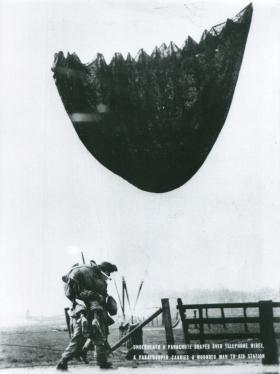 Under a parachute draped over telephone wires, a paratrooper carries a wounded man to aid.