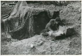 Airborne signaller at his post under a camouflaged parachute.