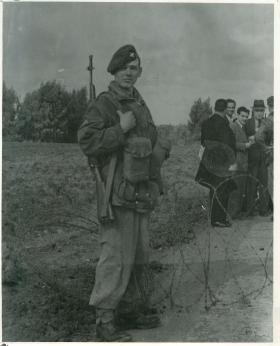 Paratrooper faces camera with barbed wire and civilians in the background. Palestine 1948.