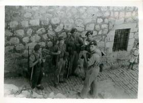 Five paratroopers have a tea break on a cobbled street in Palestine.