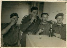 Four airborne soldiers enjoy a drink in the platoon canteen. Palestine 1946.