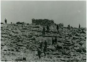 Men advancing to contact on rocky terrain.