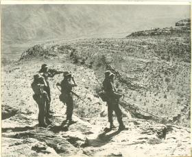 Four members of 3 PARA on patrol in a barren landscape.