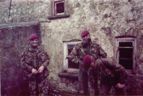 A patrol of 1 PARA stand in front of an old stone building.