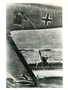 The first of a stick of German paras exits the aircraft.
