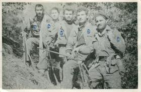 Five members of EOKA stand with weapons.