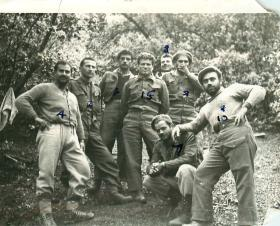 Eight members of EOKA pose for the camera in a wooded area