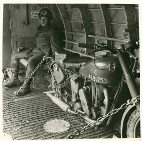 Member of 249 Field Company RE in glider with airborne motorcycle.