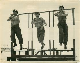 Three men jump a wooden structure for aircraft exit training.
